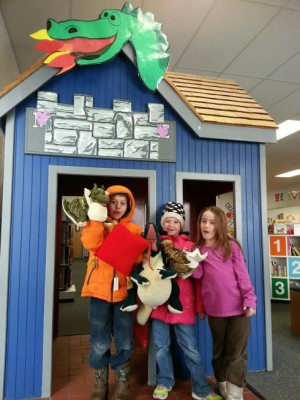 Skyler Livingston, on left, with his sisters, Kayden and Mariah, poses in front of the Dragon Depot holding his prize dragon puppet from the NB Library's Winter Reading program