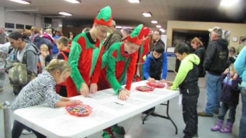 Scout Elves helped kids color a picture for Santa while they waited for their turn