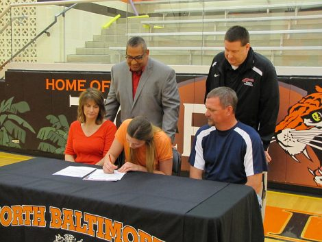 OliviaFrostSigning withPen in Hand and Coach Llanas andCoach Perry
